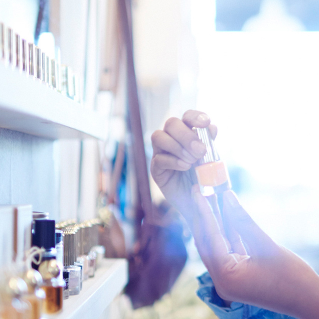 Woman examining cosmetic bottle.