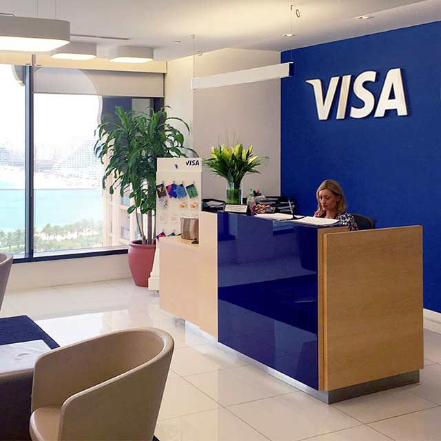 The reception area of the Dubai Innovation Center, which includes a Visa logo on the wall.